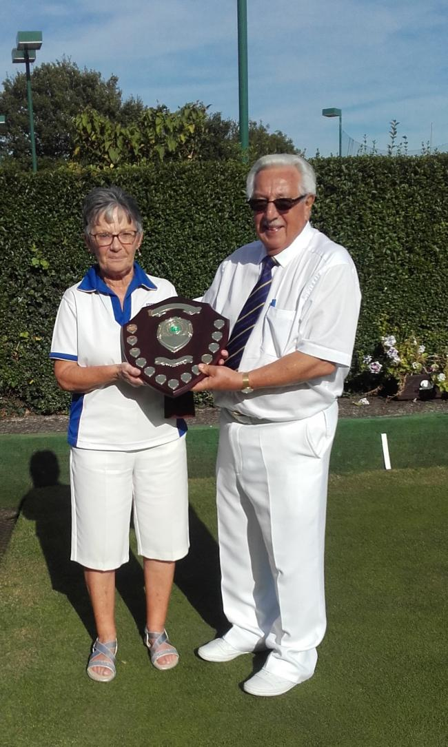Marie Hammond receving one of her titles from Epping Bowls Club captain Ron Perryman.