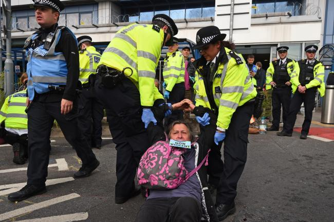 Police remove a protester from outside City Airport. Photo: PA Wire