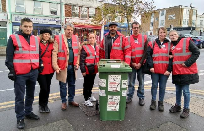 Courtney Barrett (middle, behind the bin) with his team of volunteers and the DIY knife amnesty bin. Photo credit: James Cracknell/Waltham Forest Echo