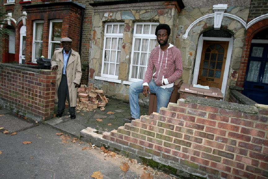 Jonah and Samuel Mensah with the damaged wall