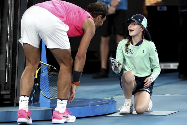 Spain's Rafael Nadal hands a ball girl his bandana after a ball hit her