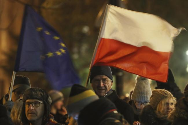 People holding a Poland and European Union flags take part in a protest outside Poland's parliament building
