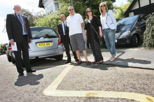 Headteacher of Woodford Green Prep School Tony Blackhurst and parents, standing over the controversial zigzag road markings