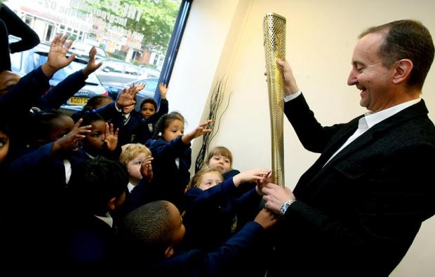 Anthony Perrett with the Olympic torch and the children from Normanhurst