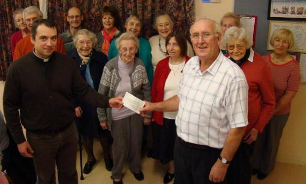 Rev Andrei Petrine presents the cheque to Ongar Club for the Physically Handicapped Club chairman Colin Green.