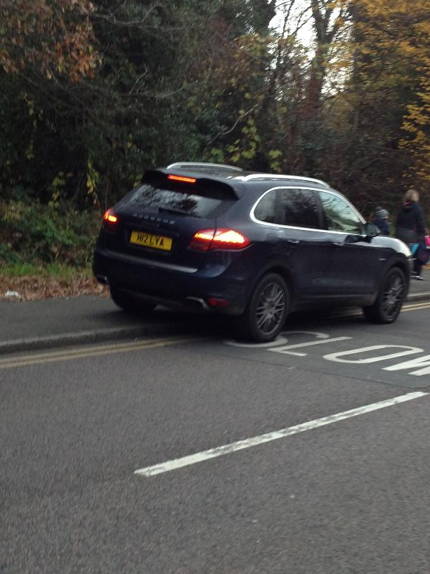 A car mounts the pavement yards from pedestrians during the school run on Whitehall Road