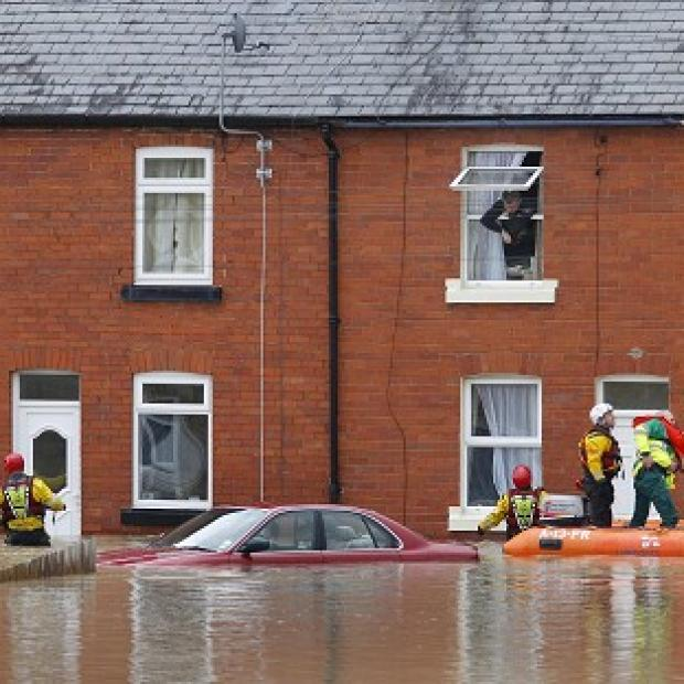 East London and West Essex Guardian Series: A man looks out of a window as a crew from the RNLI and paramedics pass a submerged car in St Asaph, Denbighshire