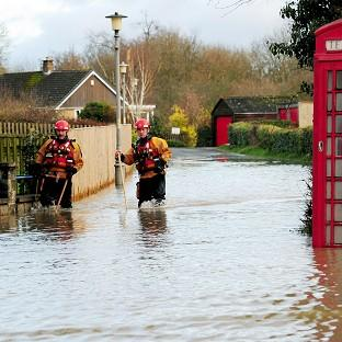 East London and West Essex Guardian Series: Firefighters make their way along a flooded street in Old Malton, North Yorkshire