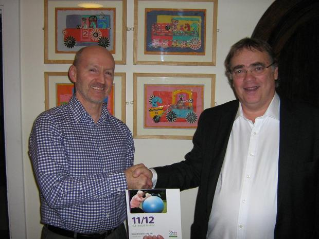 Mike Palfreman, Chief Executive of Haven House, congratulates lottery winner Peter Rose