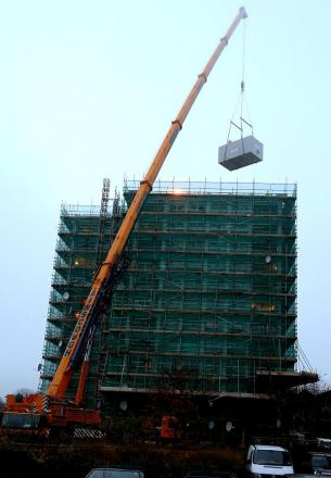 A giant crane hosts the ecopod into place on the Orchard estate