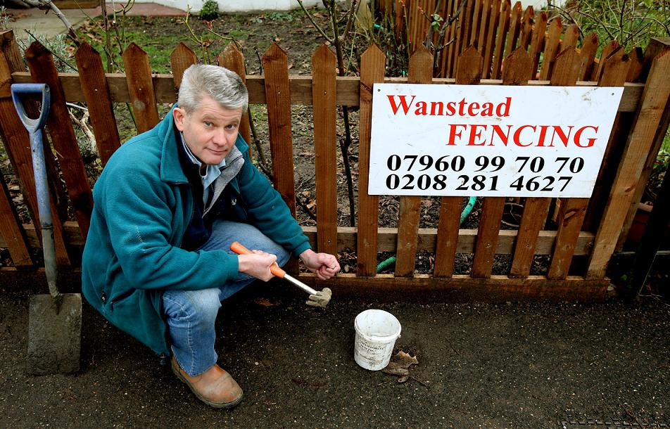 Stephen Aldridge by the sign he was threatened with a fine over.