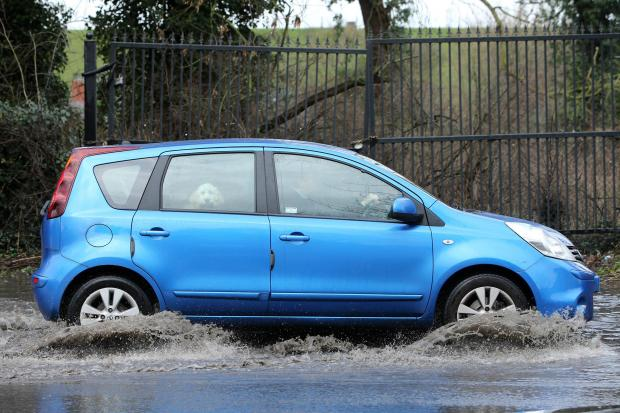 A driver negotiates the flooded area of Sewardstone Road in Chingford.