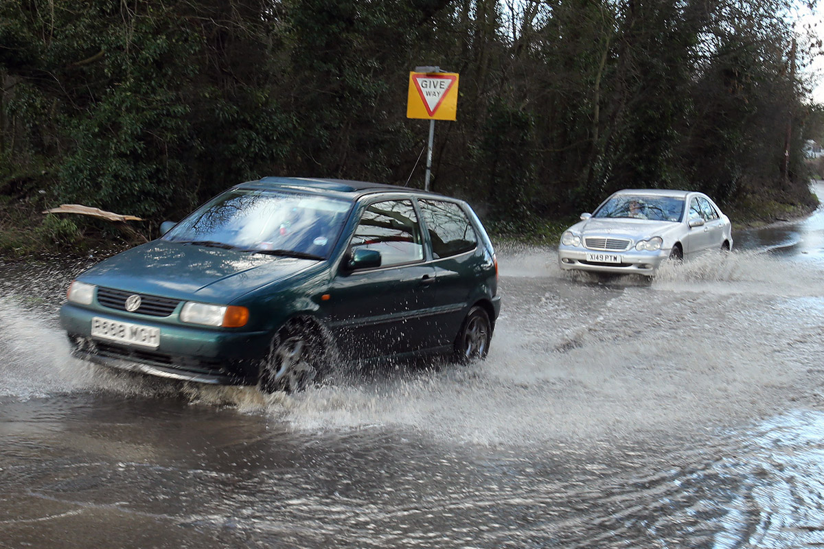 Cars drive through flooding on the B181 Epping Road at the junction of Common Road.