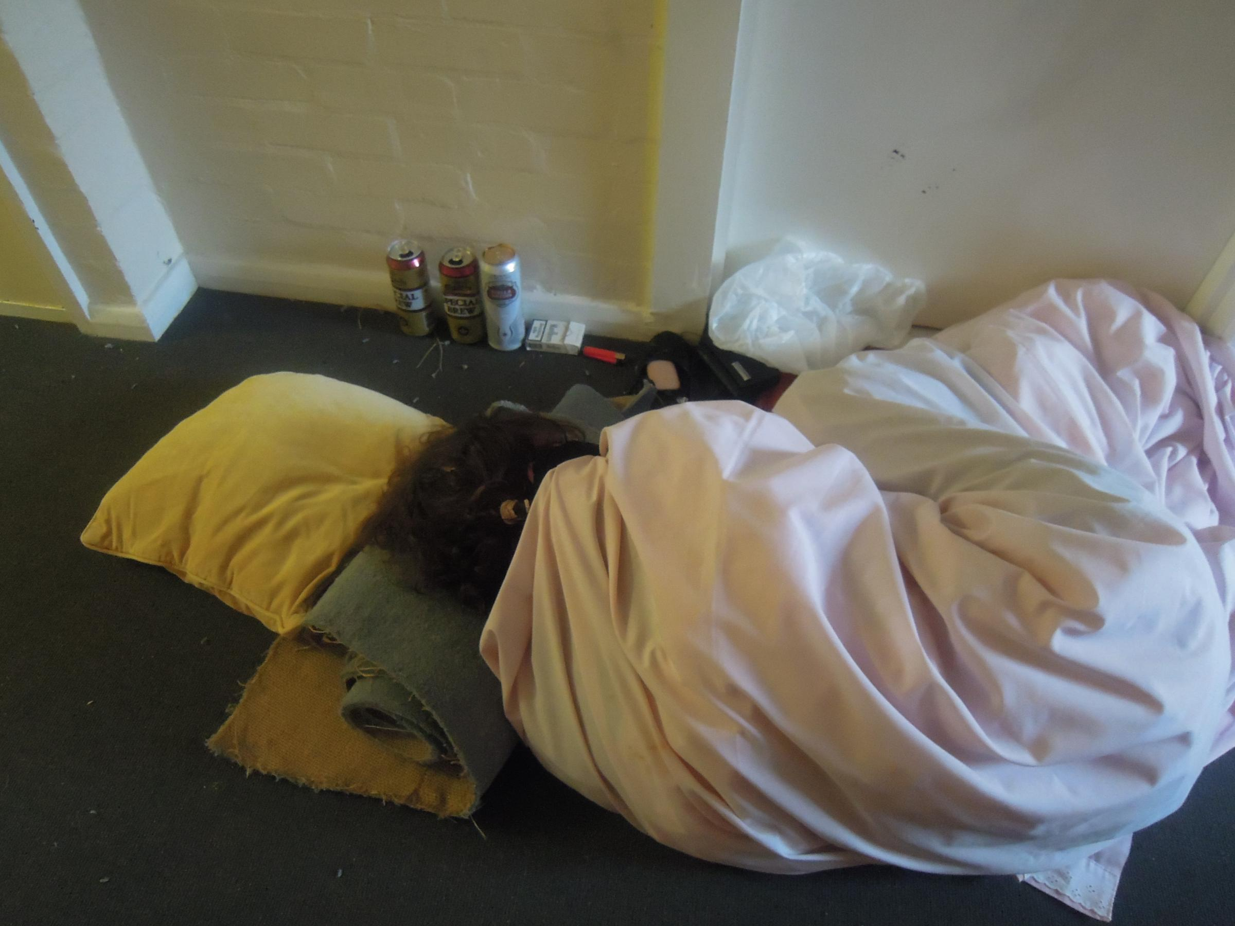 The evicted woman is pictured sleeping in a hallway in Chartwell Court