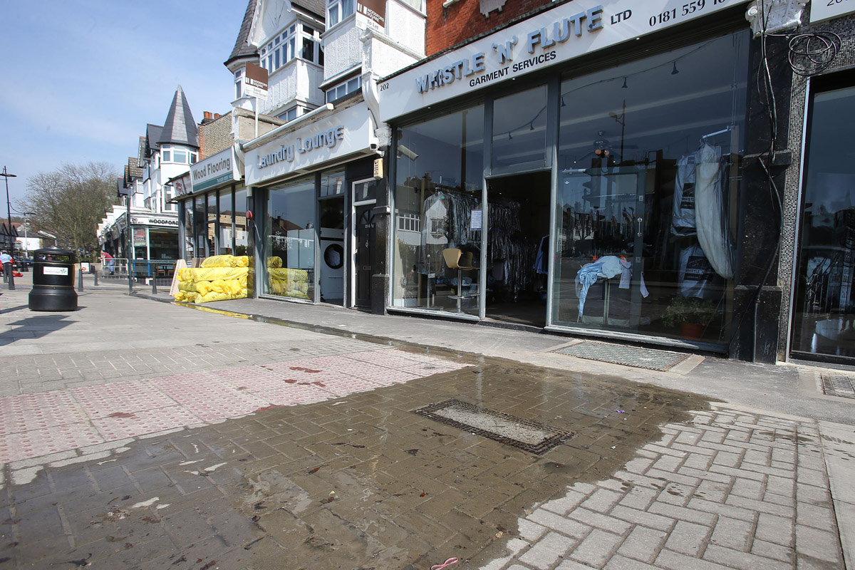 Dirty water leaking in front of shops in High Road, Woodford Green.