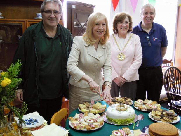 Eleanor Laing MP cuts the cake to celebrate the first birthday.  Right: Mary Sartin Chairman of Epping Forest District Council, Brian Darwood chief executive of Lighthouse Furniture Project. Left: Dave Lawrence, manager of Epping Reuse Centre