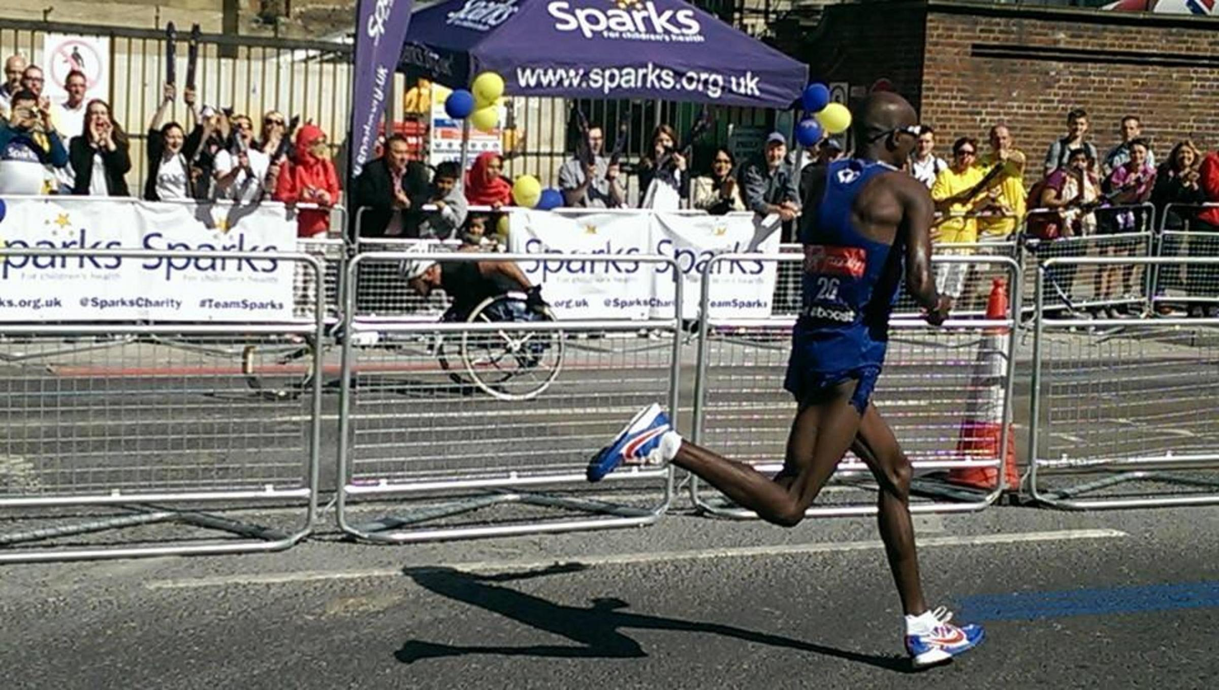 Mo Farah in the foreground with Gary Donald of South Woodford in the background at the 14-mile water station. Picture Venissa Amin