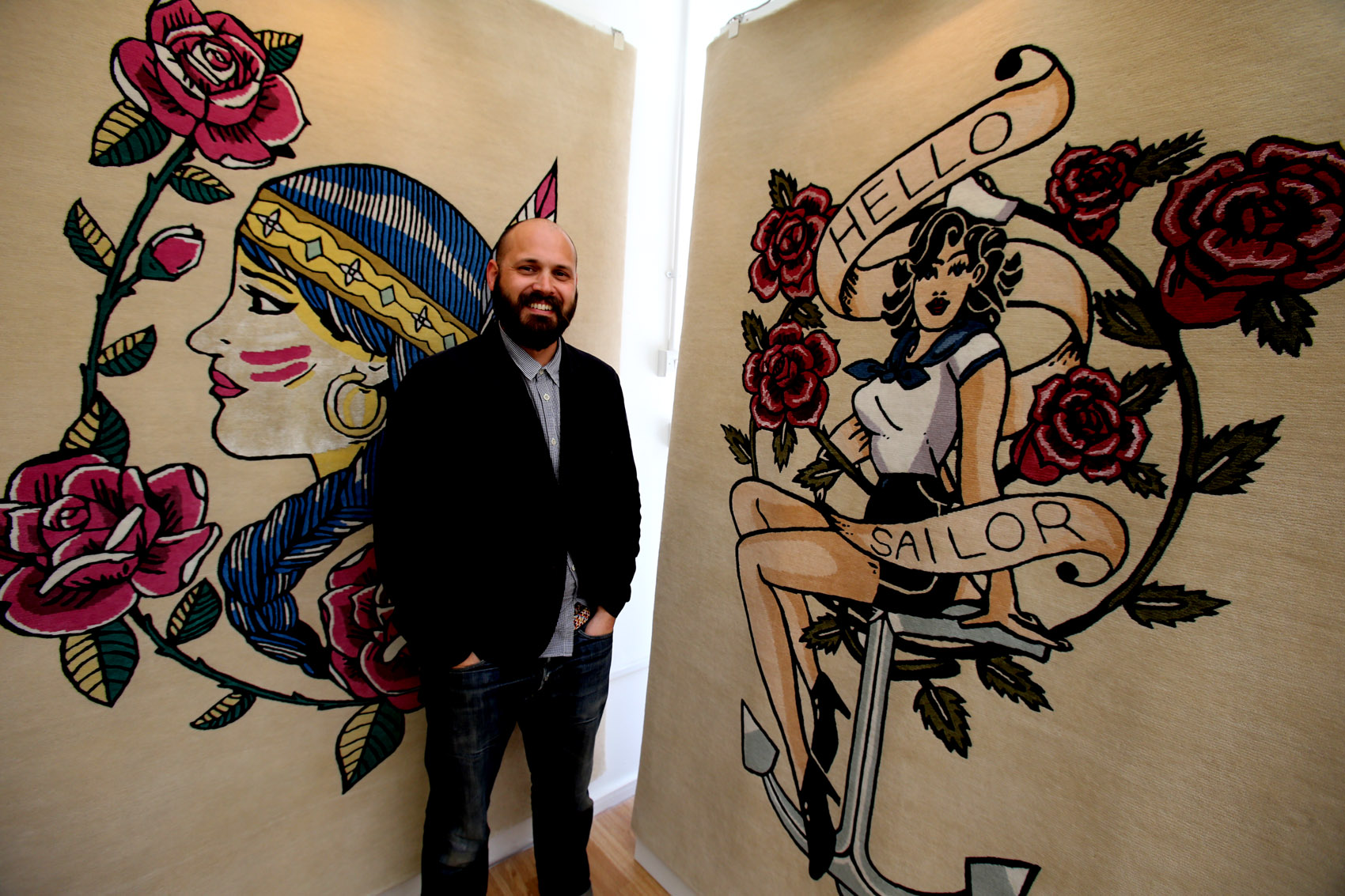 Simon Goff with two 1950s tattoo inspired rugs in the Hoe Street pop-up shop