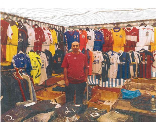 Abdul Kadir Ozkok at a market stall surrounded by counterfeit goods imported from Turkey