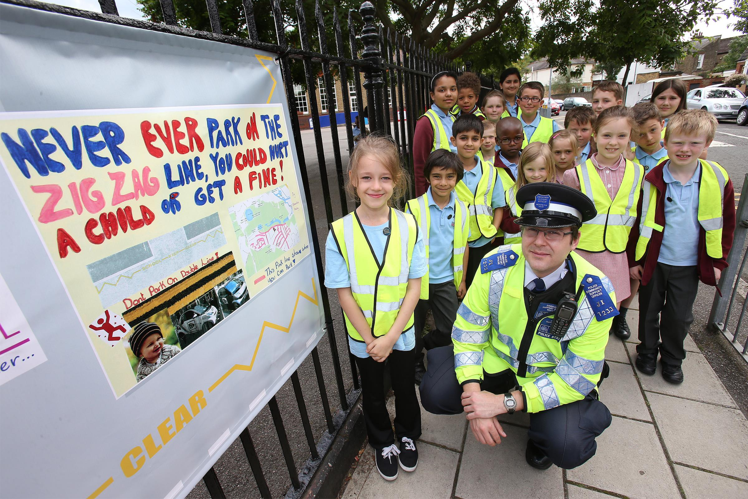 Alexandra Brady shows PCSO Alan Winston and classmates her banner designed to promote road saftey outside Aldresbrook Primary School