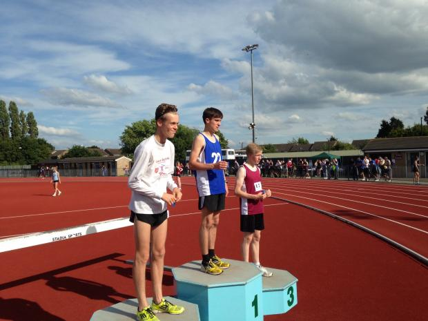 Daniel Richards (middle) collects his gold medal in the boys 1500m.