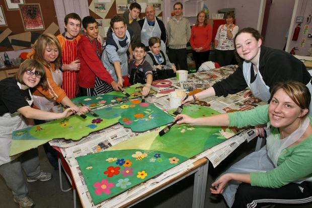 Volunteers and pupils busy painting for the sensory garden at Oak View School