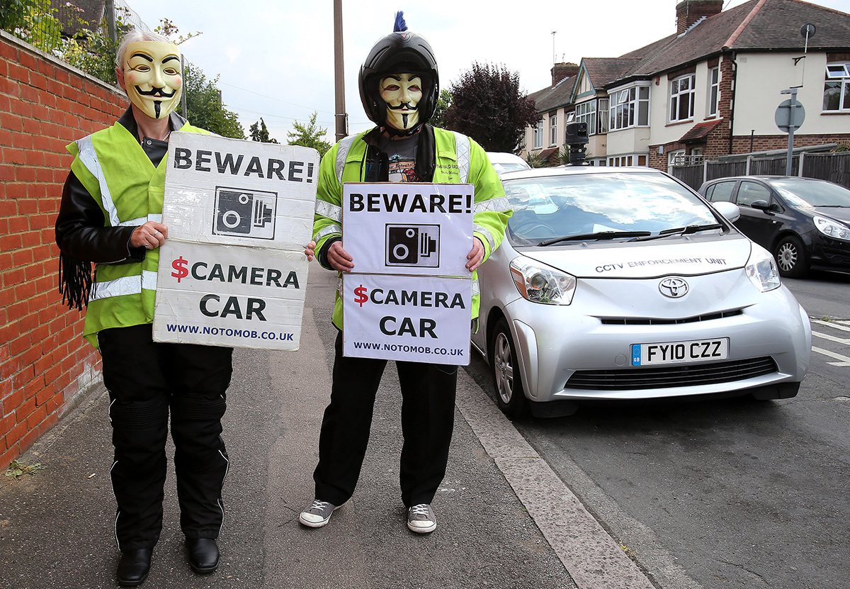 Trish and Steve Baker of  No To Mob beside a CCTV spy car in Tufton Road, Chingford.