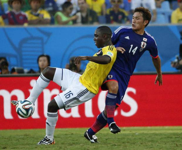 East London and West Essex Guardian Series: Eder Alvarez Balanta (left) fights for the ball with Japan's Toshihiro Aoyama (right). Picture: Action Images