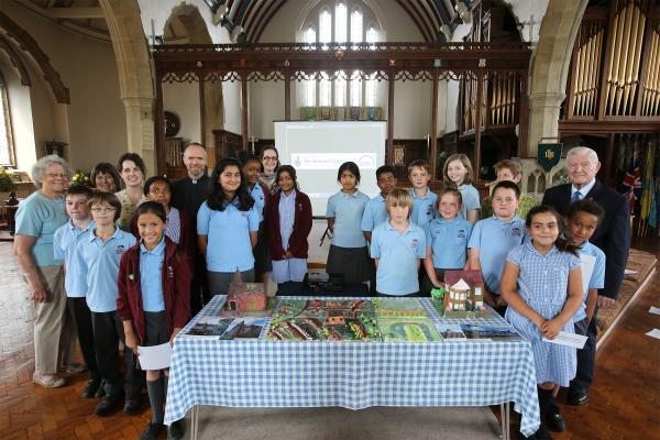 Vicar Martyn Hawkes (eighth from left) with students and staff from Aldersbrook Primary School.