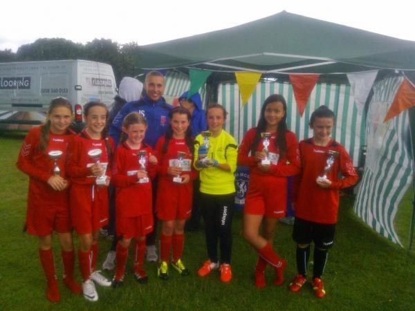 The victorious LOASS Under-11 squad pose with their trophies.