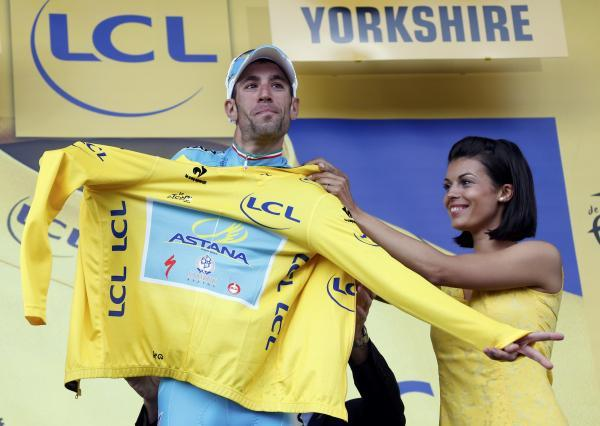 Vincenzo Nibali pulls on the yellow jersey. Picture: Action Images