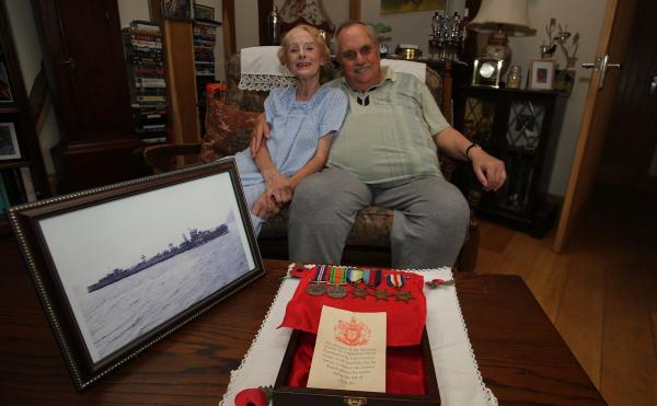 Harold Thain with wife Patti Lynn and a picture of HMS Vidette, which he served on for D-Day