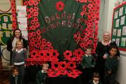 Oakdale Infants Schoool pupils with the poppy display they have created to mark Remembrance Day with teachers Miss Hegarty and Miss Wright (EL81057_1)