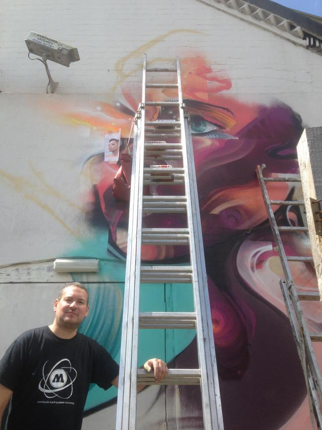 Mr Cenz in front of his artwork on Hurricane Room pool club