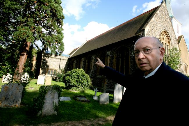 Trevor Jones points to the roof of St Mary's Church, in Chigwell, from where lead was stolen