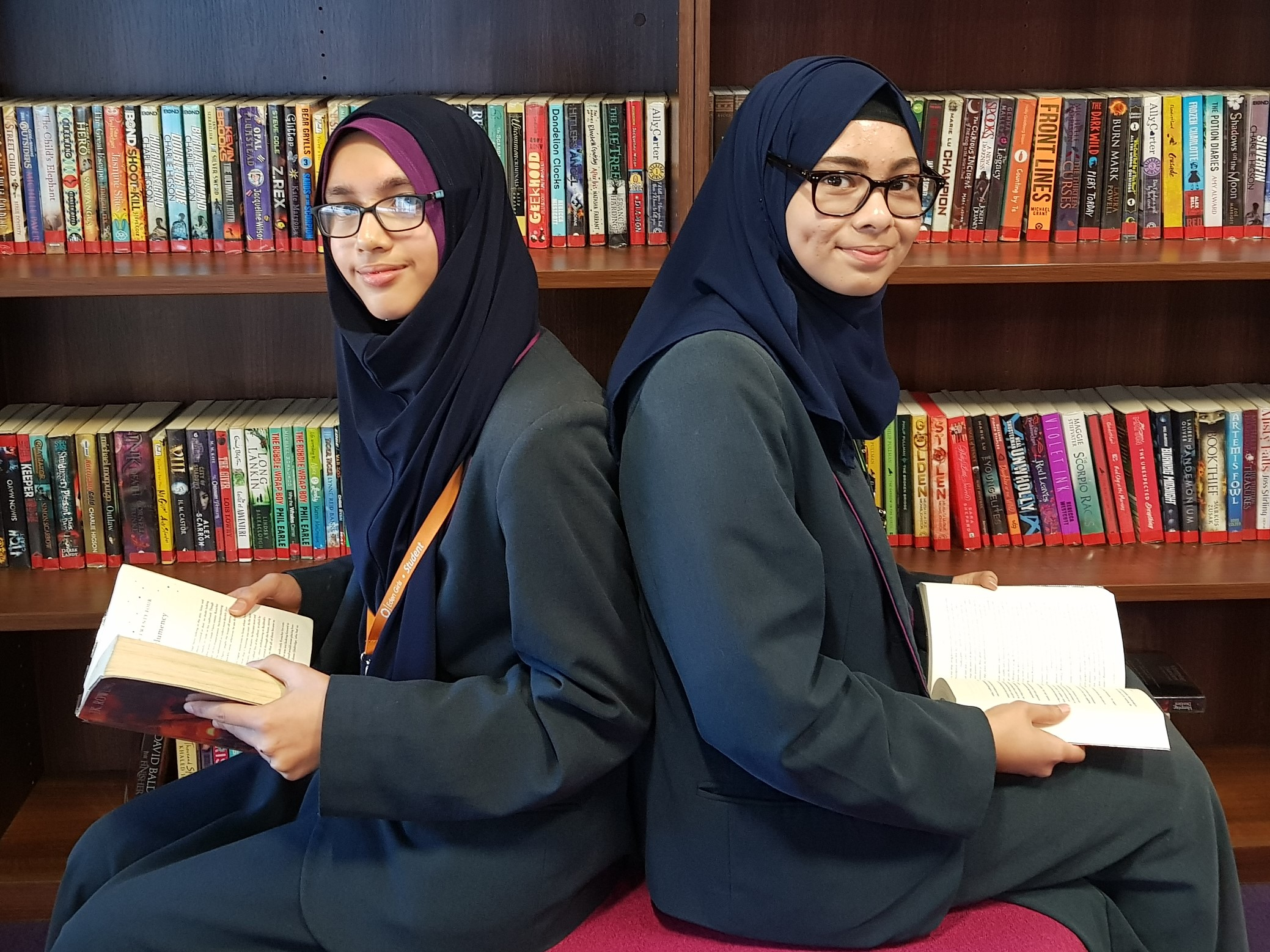 Students Rabia Shaikh and Badriyah Islam put their prize money towards new books for their school library.