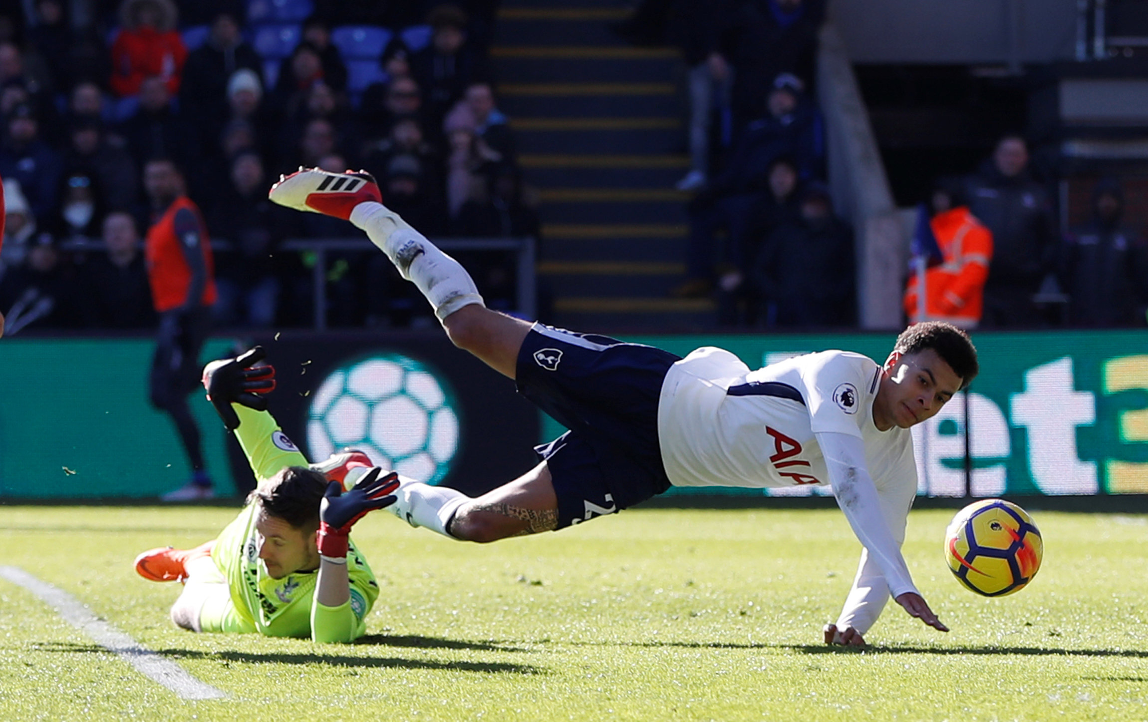 Dele Alli takes a tumble following Wayne Hennessey's challenge. Picture: Action Images