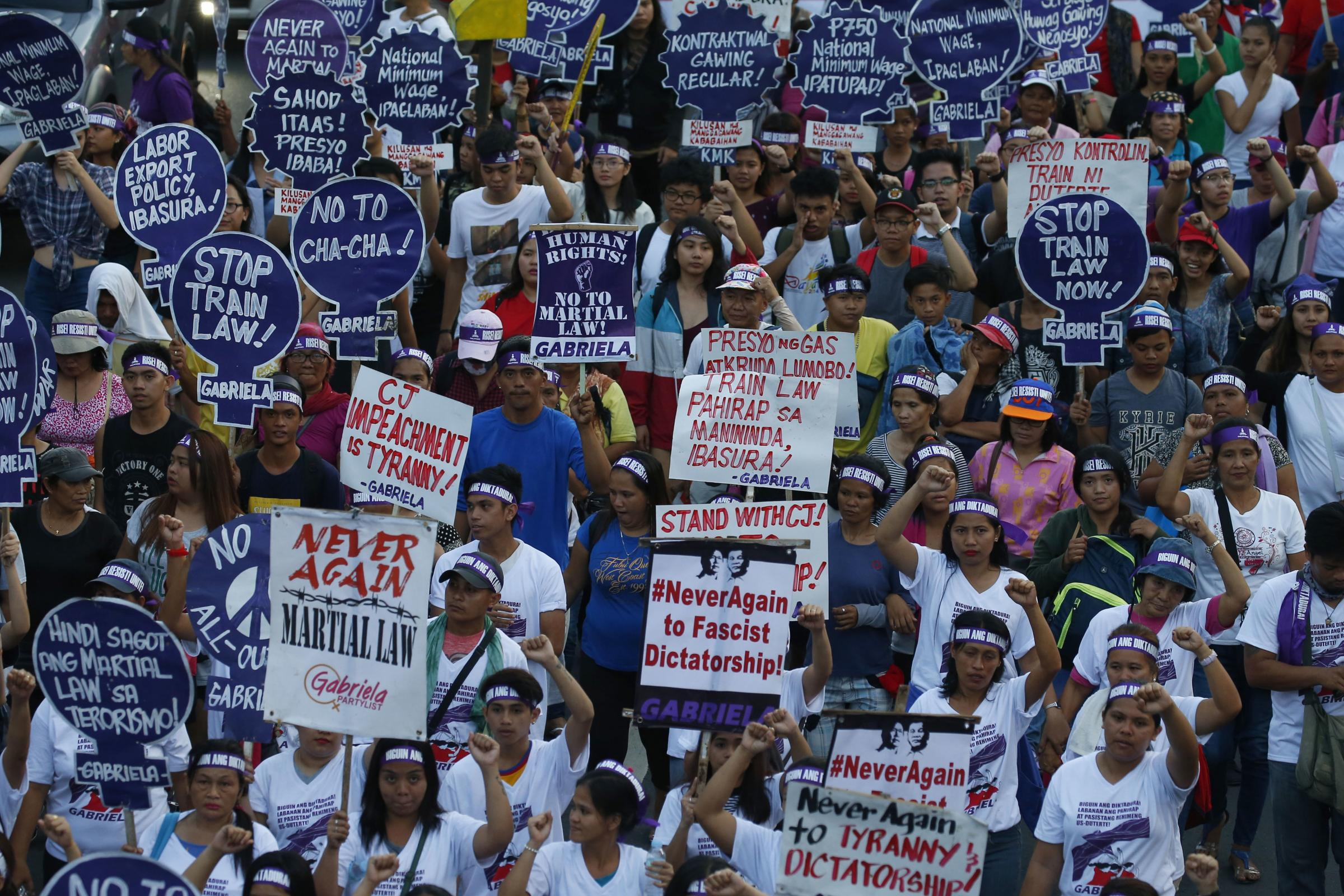 Protesters march towards Presidential Palace in Manila, Philippines, to mark International Women's Day (AP)