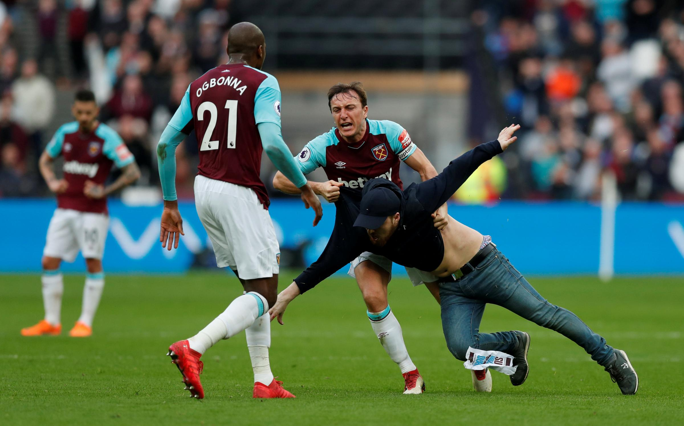 Mark Noble wrestles the first pitch invader to the ground. Picture: Action Images