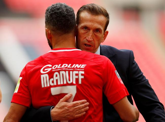 Justin Edinburgh embraces Jobi McAnuff after the full-time whistle. Picture: Action Images